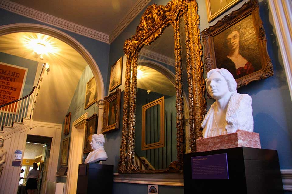 The Belmont-Paul Women's Equality National Monument house's entryway with stunning gold frames and two white busts on an interior blue wall.