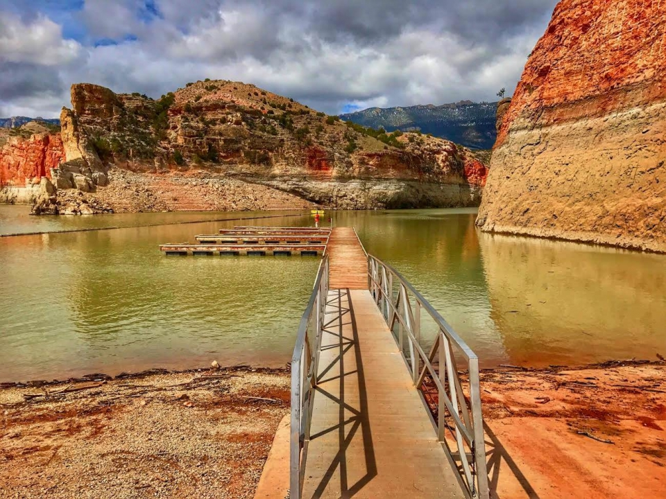 A dock in the lake at Barry's Landing surrounded by striated red sandstone cliffs at Bighorn Canyon National Recreation Area