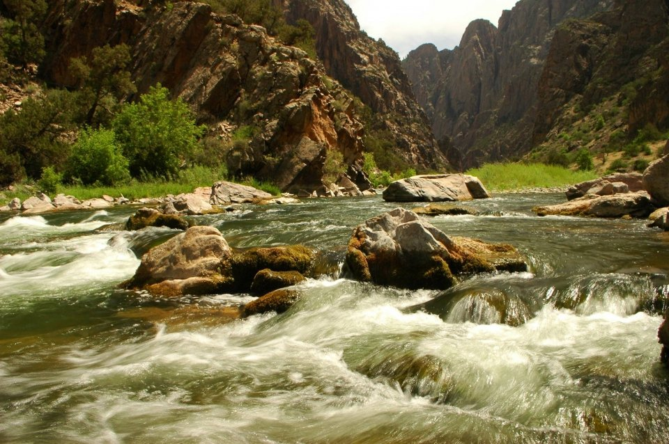 The waters of the Colorado River cascading over rocks at the bottom of the Black Canyon of the Gunnison