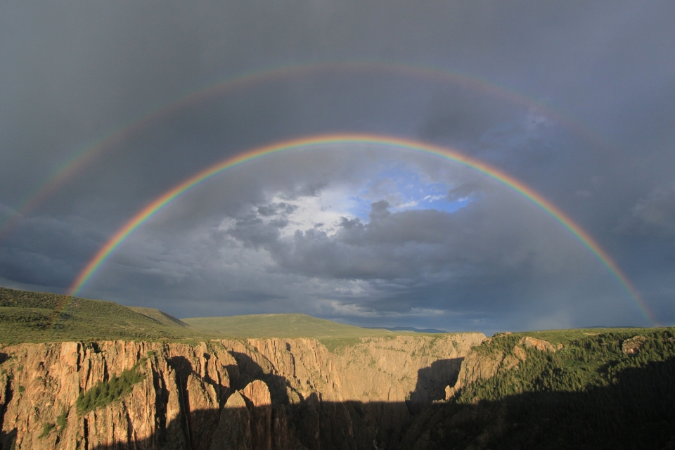 Full semi-circle double-rainbow in front of cloudy skies over the Black Canyon of the Gunnison National Park