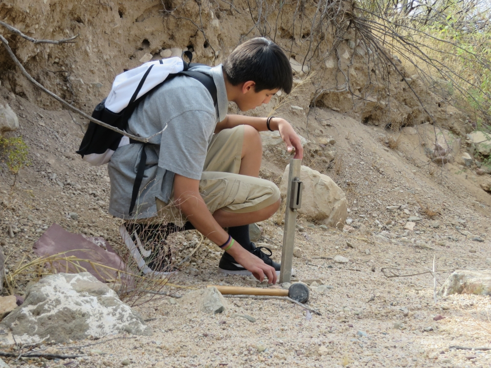 A Native American student taking science measurements at Saguaro National Park