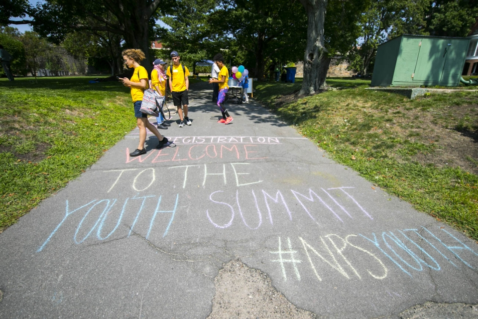 "A group of young visitors walk in to registration for the Youth Summit. On the paved path, in chalk, is written ""Welcome to the Youth Summit #NPSYouth"""