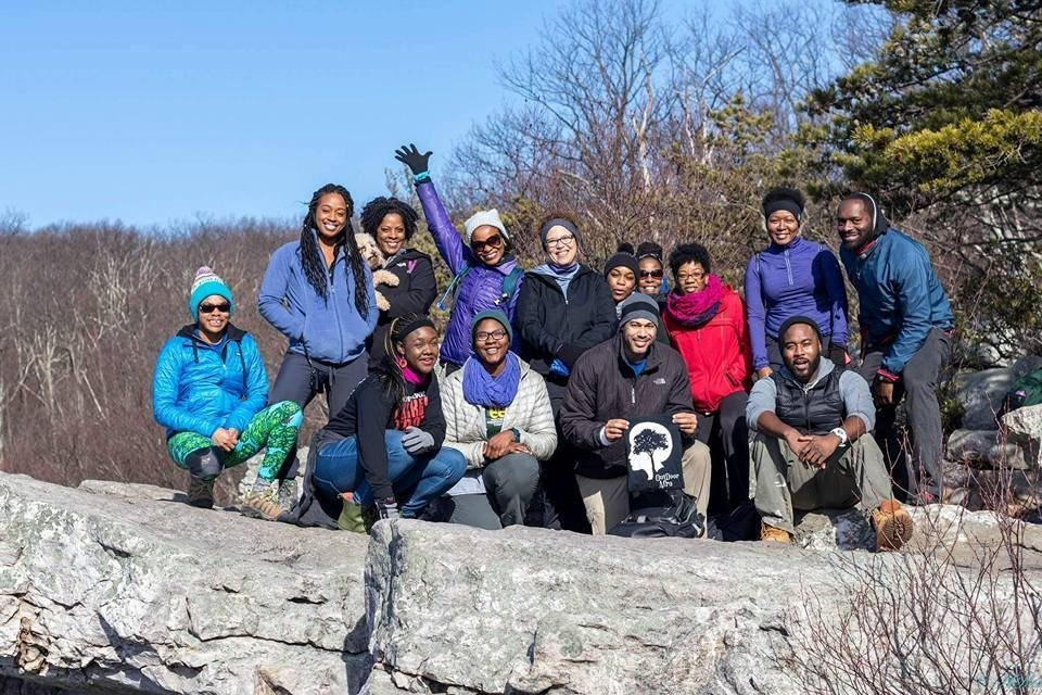 Large group of smile at the top of rocks in a park. One person is holding a black and white Outdoor Afro t-shirt