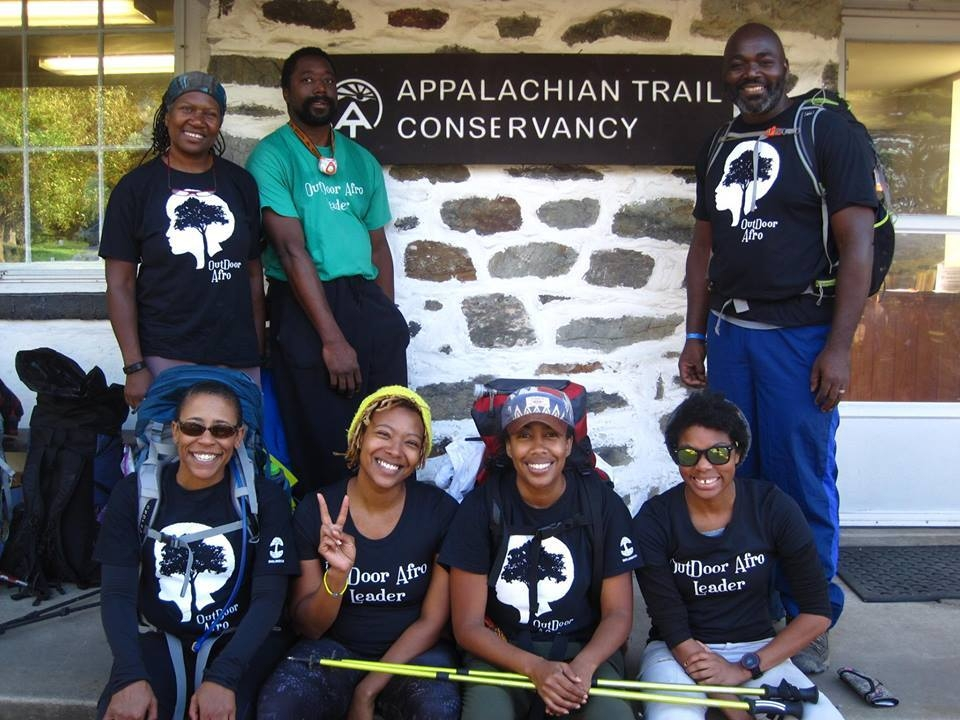7 people wearing Outdoor Afro t-shirts pose with the Appalachian Trail Conservancy sign, posted to a stone building.