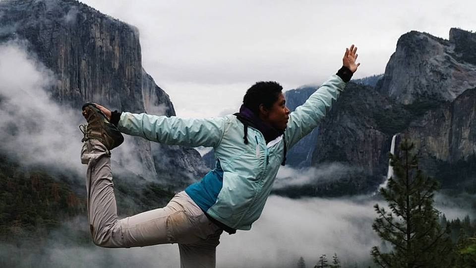 Young female doing a yoga pose, arm outstretched and foot lifted with blue and green covered mountains and white fog in the background