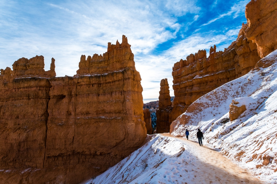 Two people hiking in the winter on a trail amongst the red cliffs at Bryce Canyon National Park