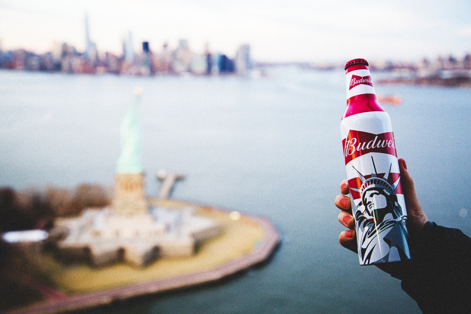 Statue of Liberty packaging on Budweiser bottle, held in frame with Statue of Liberty National Monument in the distance