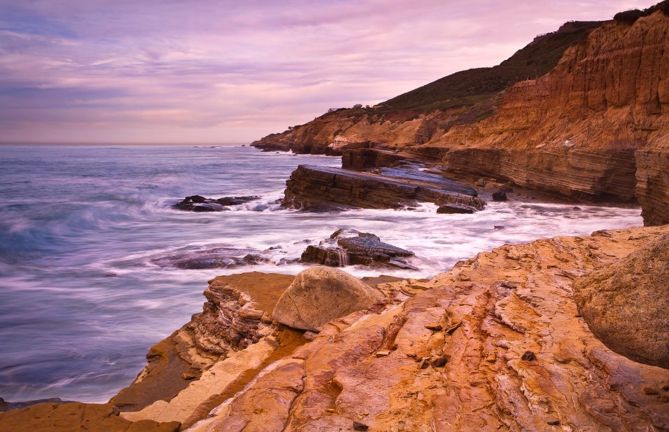 High tide waves crash against orange-tinged cliffs as a purple sky stretches overhead.