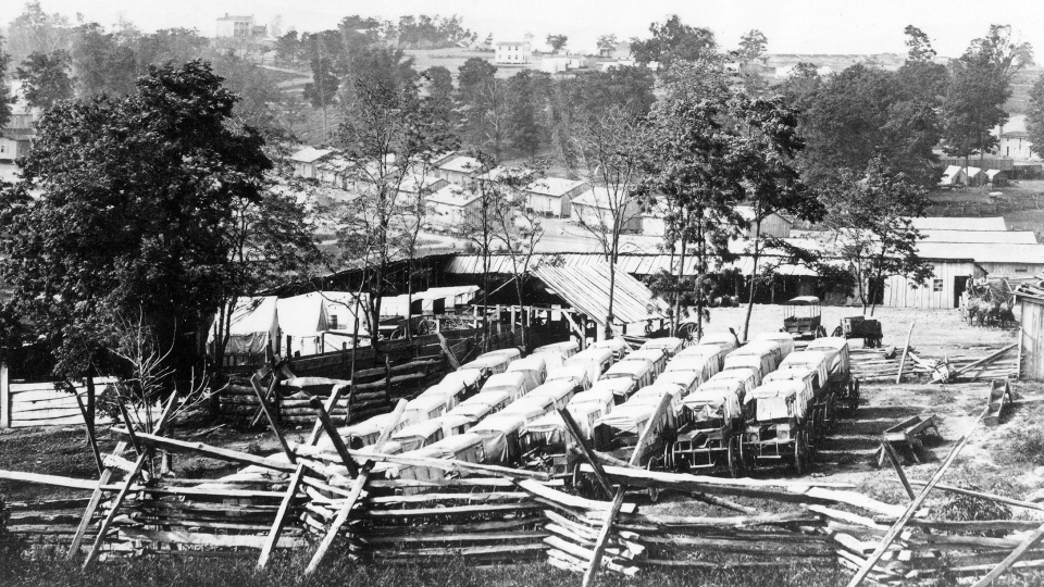 Historic black and white photo of vehicles and barracks at Camp Nelson National Monument