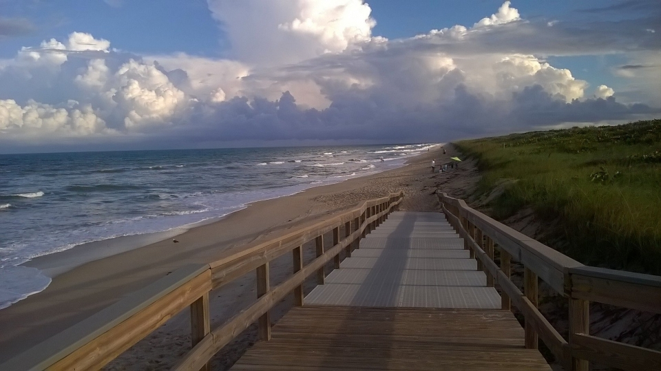 Wooden boardwalk ramp down to the sandy beach of Canaveral National Seashore