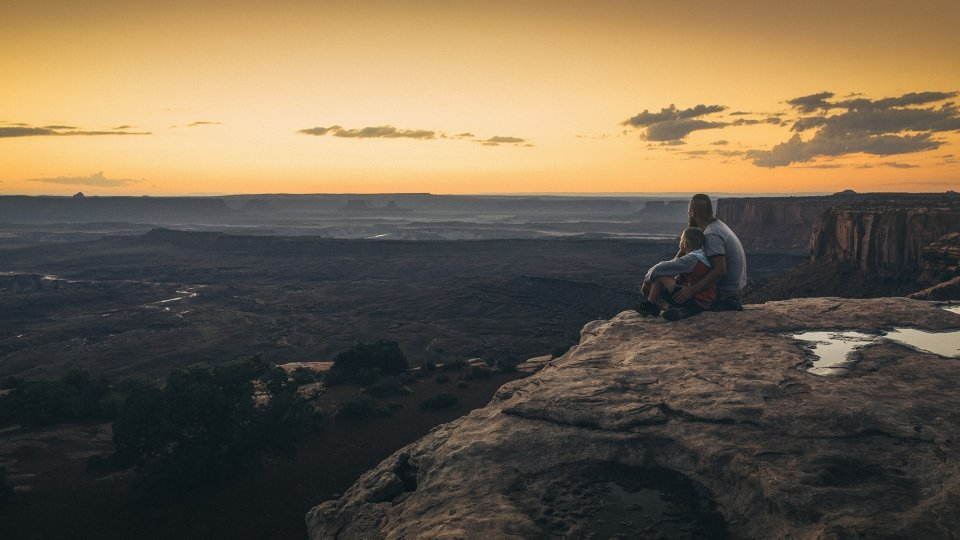 Father and son sitting on the edge of cliff overlooking vast landscape at Grand View Point of Canyonlands National Park during sunset