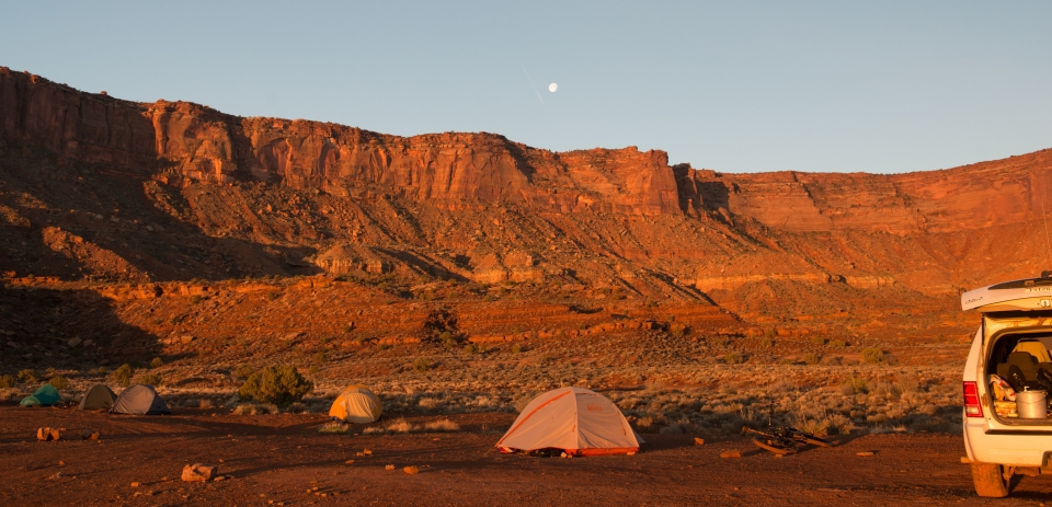 Tents scattered around a flat area with tall orange cliffs and the moon in the distance - Canyonlands National Park