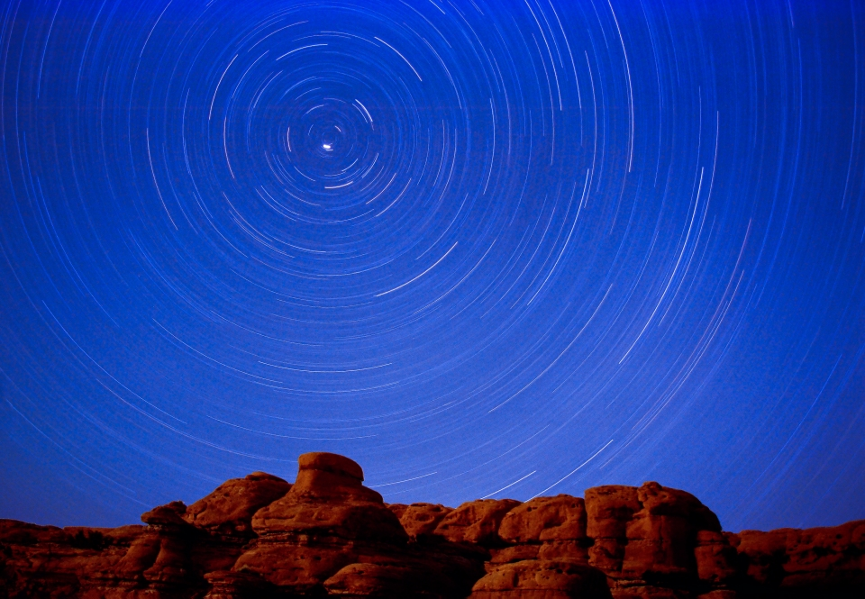 The stars seemingly swirl above the red rocks of Canyonlands National Park.
