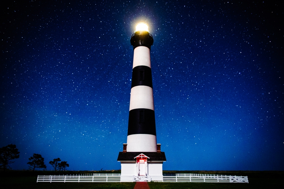 The Bode Island Light Station shines brightly against a blue night sky at Cape Hatteras National Seashore.