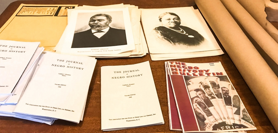 """Papers on a table that include images of Carter G. Woodson and Mary McLeod Bethune, """"The Journal of Negro History"""", and """"The Negro History Bulletin"""""""
