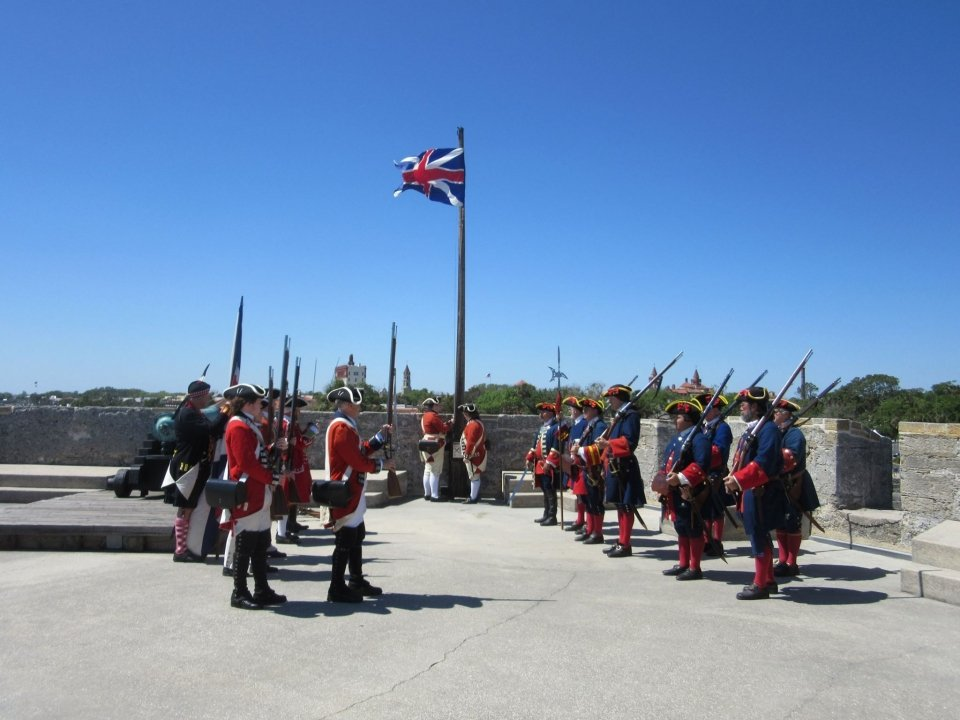British and American soldiers with the British flag flying at Castillo De San Marcos National Monument