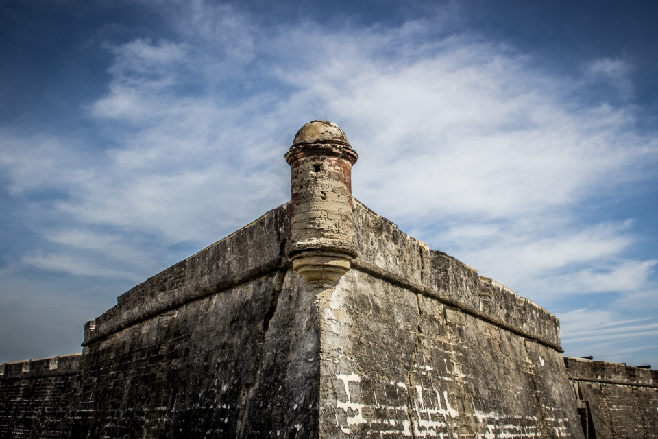 A watch tower from the southwest bastion of the castillo is centered with a cloudy sky in the background