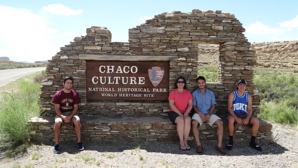 A group of visitors sit around the sign for Chaco Culture National Historical Park