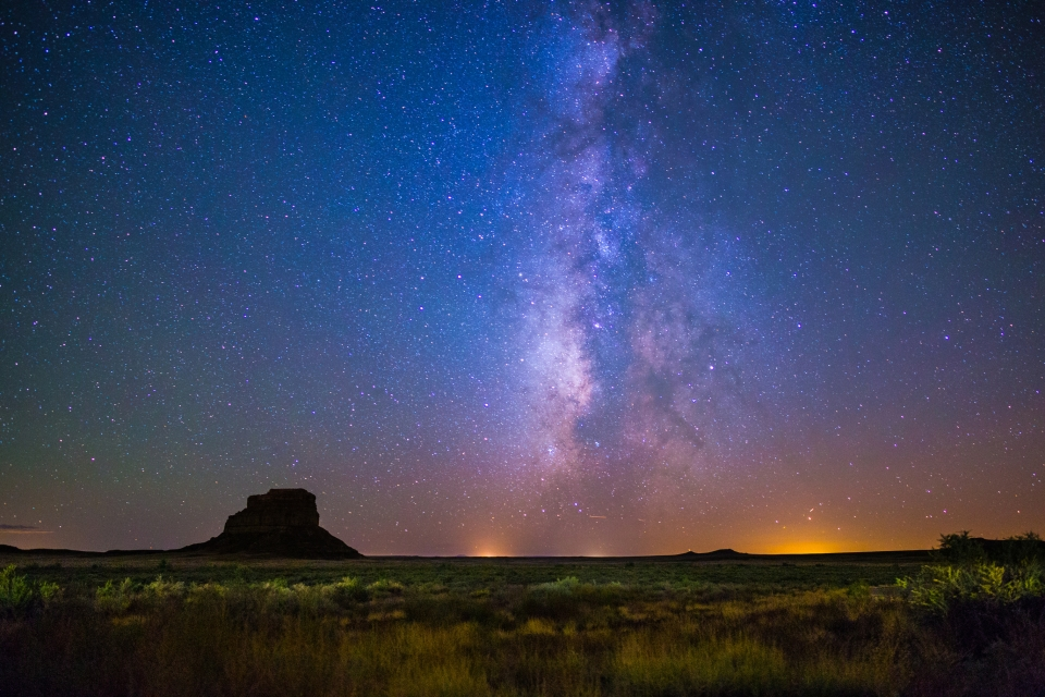 Fajada Butte stands in silhouette against the night sky and Milky Way