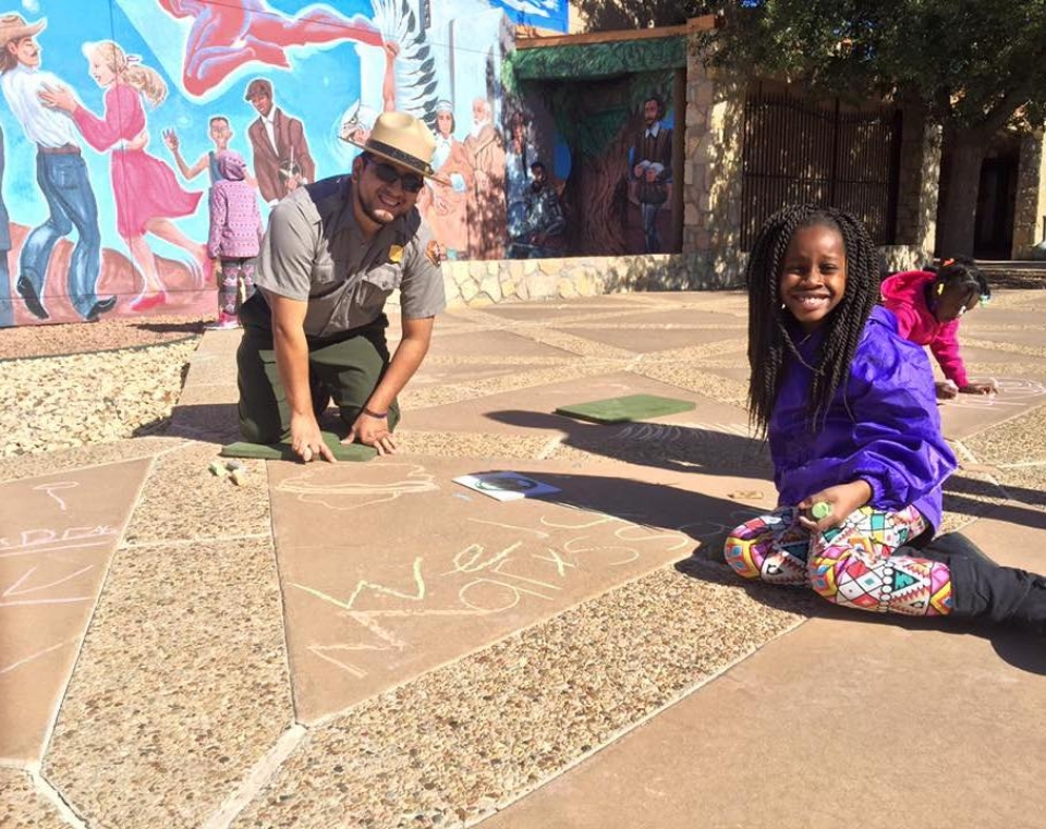Ranger and a young student sitting on a chalk-drawn ground and smiling at Chamizal National Monument