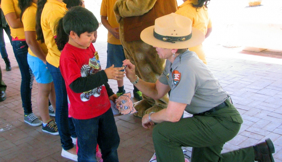 Young boy receiving his Jr. Ranger badge from a kneeling park ranger at Chamizal National Monument
