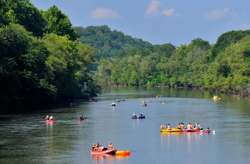 Inflatable rafts and canoes floating on a wide river surrounded by green trees at Chattahoochee River National Recreation Area
