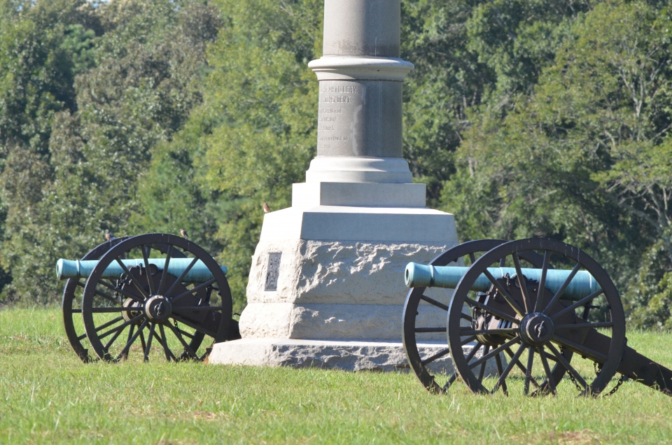 Two cannons in a sunny field with a stone monument in between them, Chickamauga & Chattanooga National Military Park