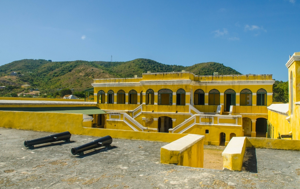 The yellow walls of Fort Christianvaern contrast against mountains and a blue sky in Christiansted National Historic Site