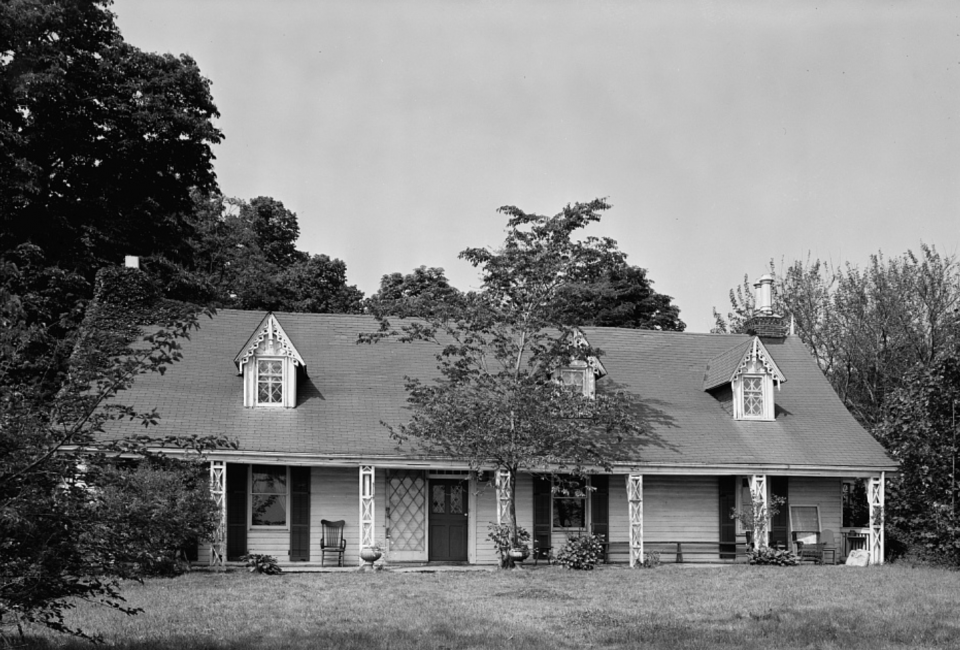 Black and white photo of a two-story house with a small garden out front