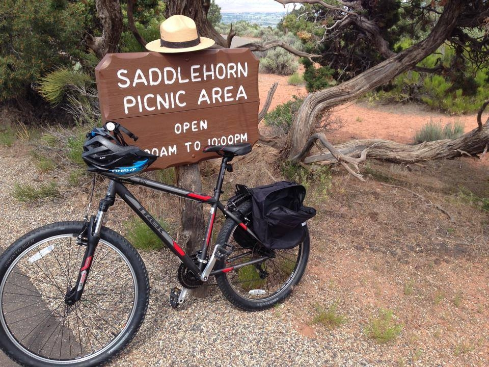 """Wooden sign saying """"Saddlehorn Picnic Area"""" with a bike and a ranger hat at Colorado National Monument"""