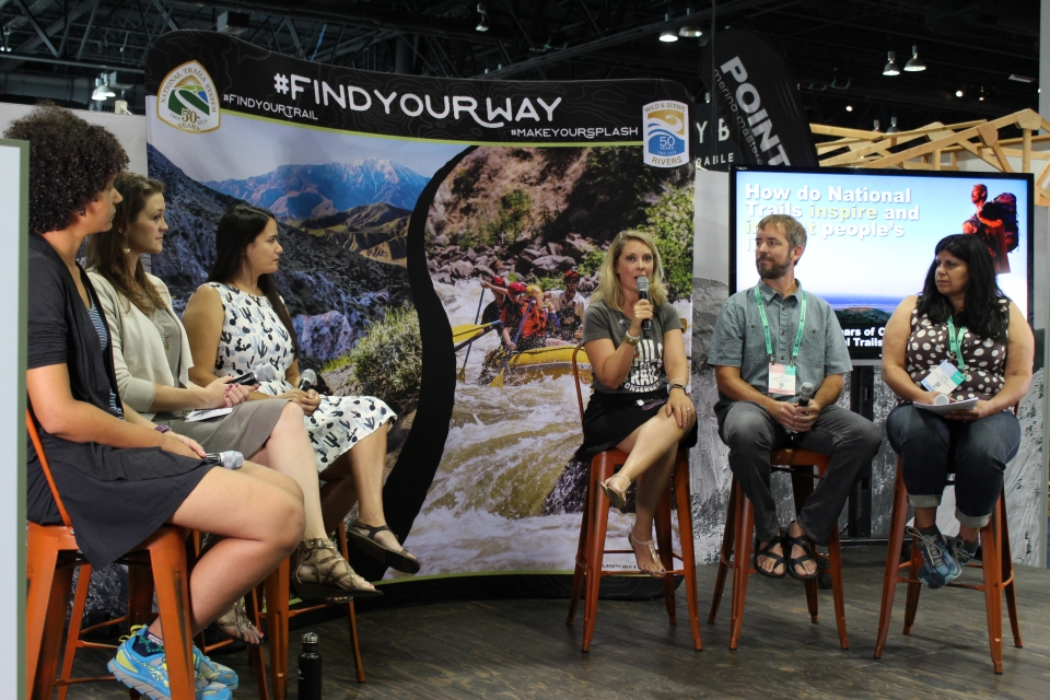 Six people sit in a semi-circle on stools during a presentation. A banner behind them has a pictures of two trails.
