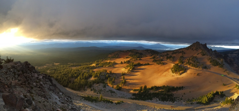 The sun setting on the brown hills of Crater Lake National Park as storm clouds roll in