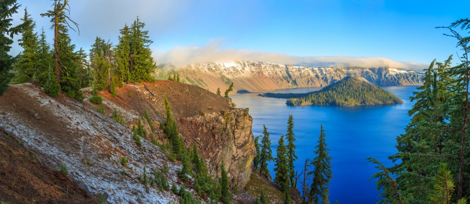 A tree-covered island in the middle of a blue Crater Lake, with the surrounding hills covered in a light dusting of snow