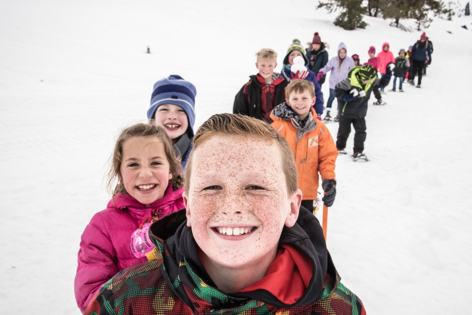 A group of smiling kids on snowshoes in the snow at Craters of the Moon National Monument and Preserve