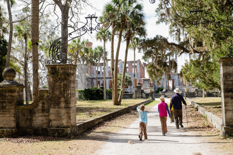 A family walking towards the ruins at Cumberland Island National Seashore