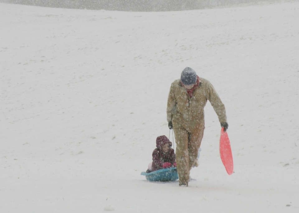 A child rides a teal plastic saucer, pulled in the snow by their parent, holding their own plastic saucer
