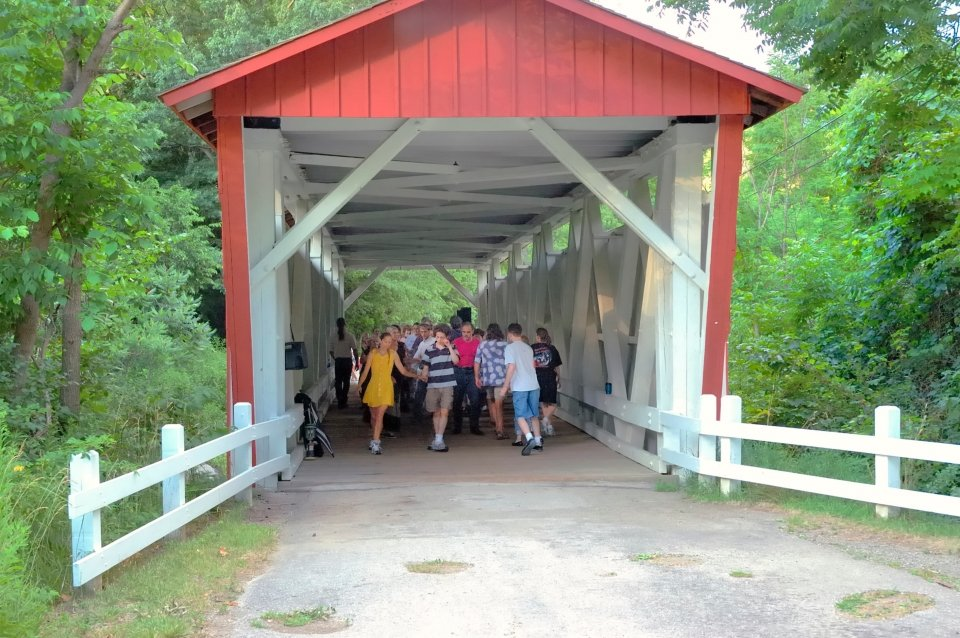 A group of people dancing contra dance under a covered bridge at Cuyahoga Valley National Park