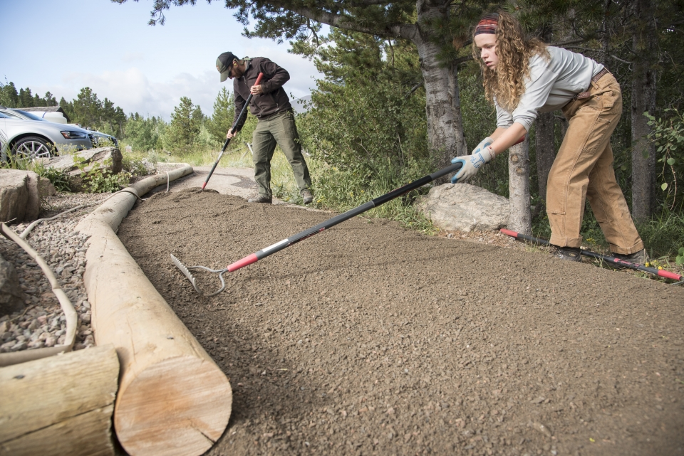 Youth raking and ground to build trail