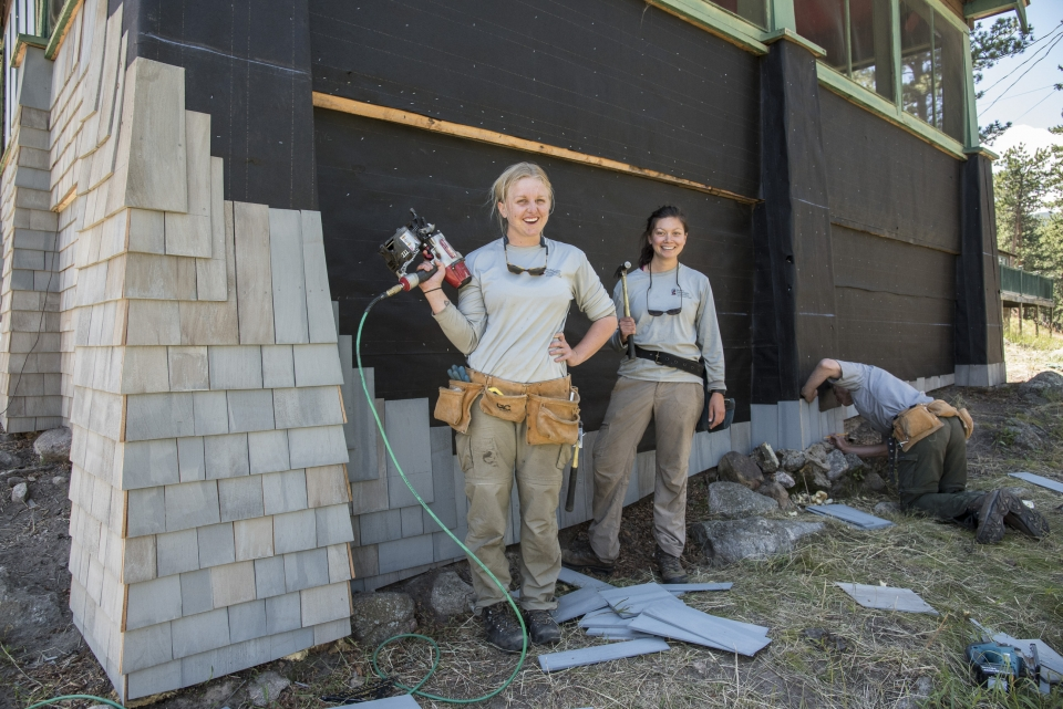 Two girls, one holding a power drill and another holding a hammer, working on construction on a building at Rocky Mountain National Park