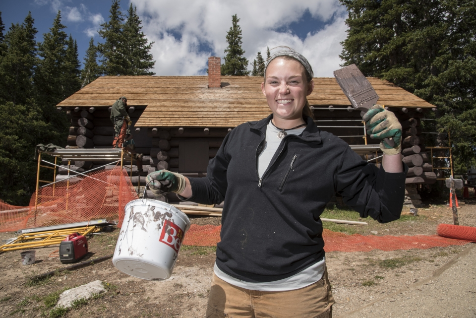 Beaming female youth with paint brush and paint bucket in hands