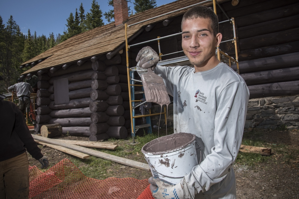 Young man with a can of paint holding up a paintbrush ready to paint the log cabin being constructed at Rocky Mountain National Park