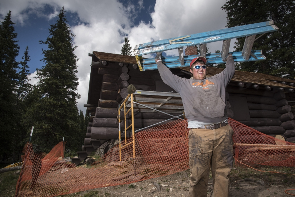 Laughing youth with sunglasses holding a ladder above his head, working on construction at Rocky Mountain National Park