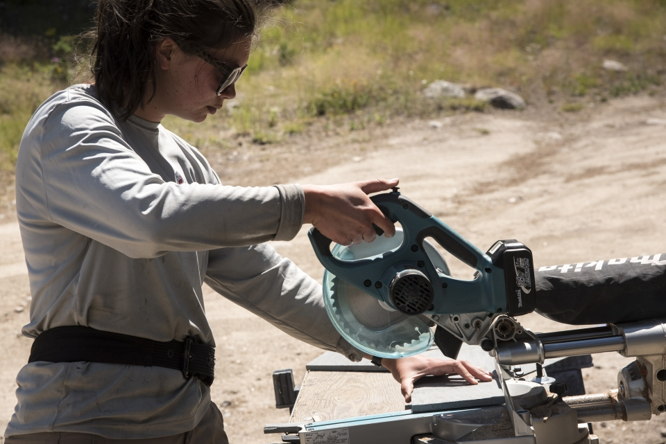 Female teen using a circular saw for trail work at Rocky Mountain National Park