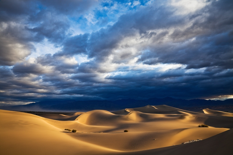 Dramatic storm clouds gathering in the blue sky over the sun-lit dunes of Death Valley National Park