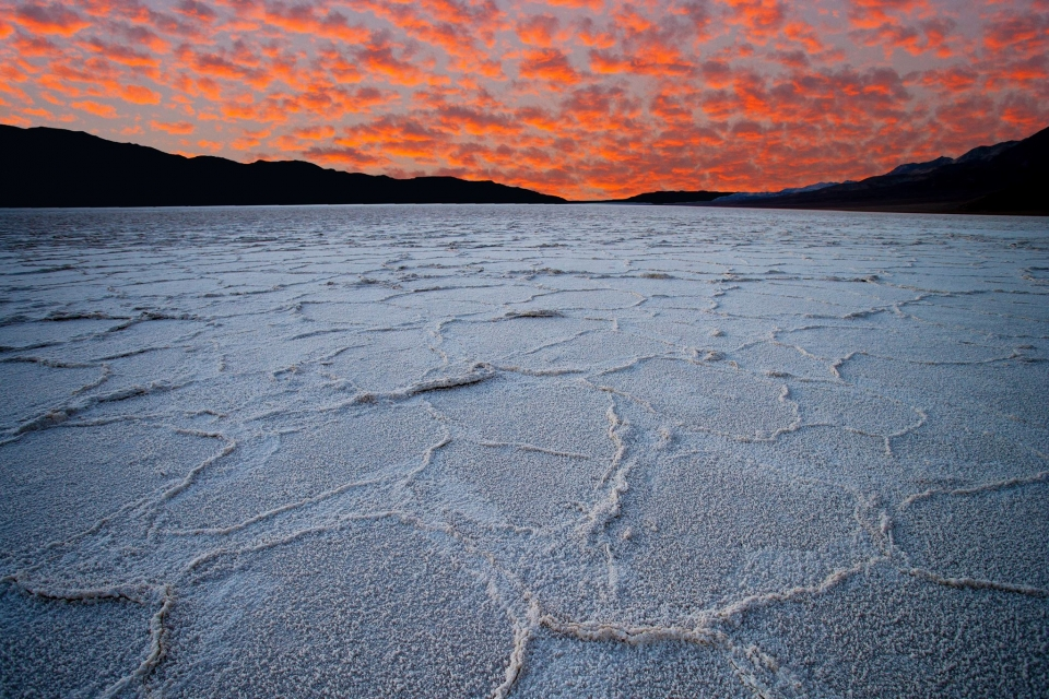 Neon orange and pink fluffy clouds over a the white salt flats of Badwater Basin at Death Valley National Park