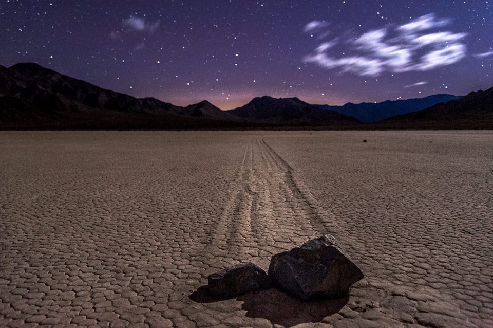The night stars shine in the purple-blue sky over a sailing rock at Racetrack Playa in Death Valley National Park