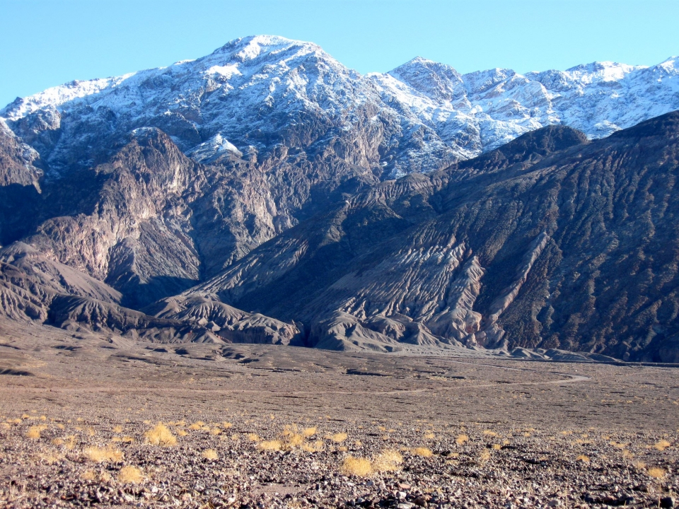 Snow-dusted Black Mountains behind a desert landscape at Death Valley National Park