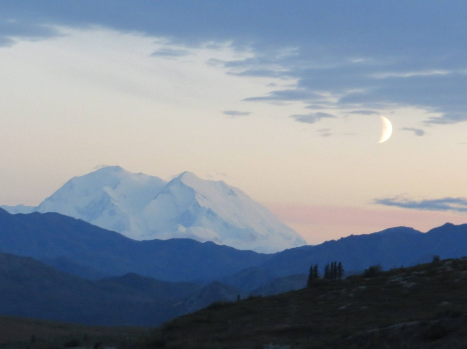 A crescent moon hovers over the snow-capped mountains of Denali National Park & Preserve.