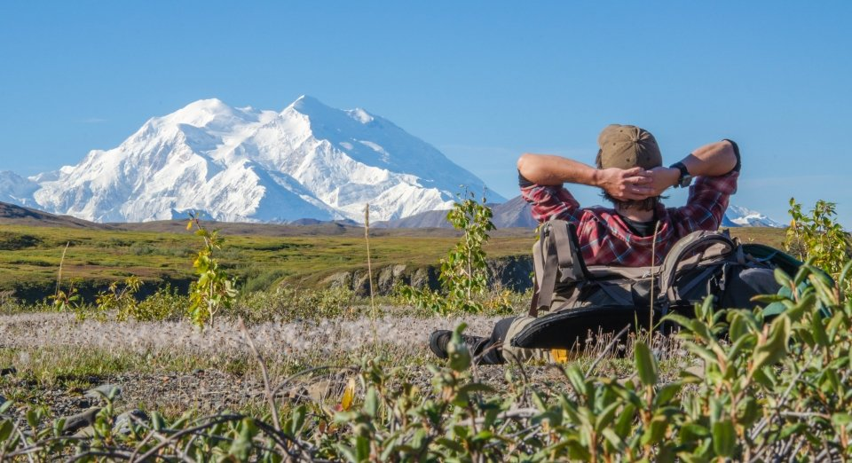 Man lying on his back against his backpack while looking up at the snow-covered mountain at Denali National Park