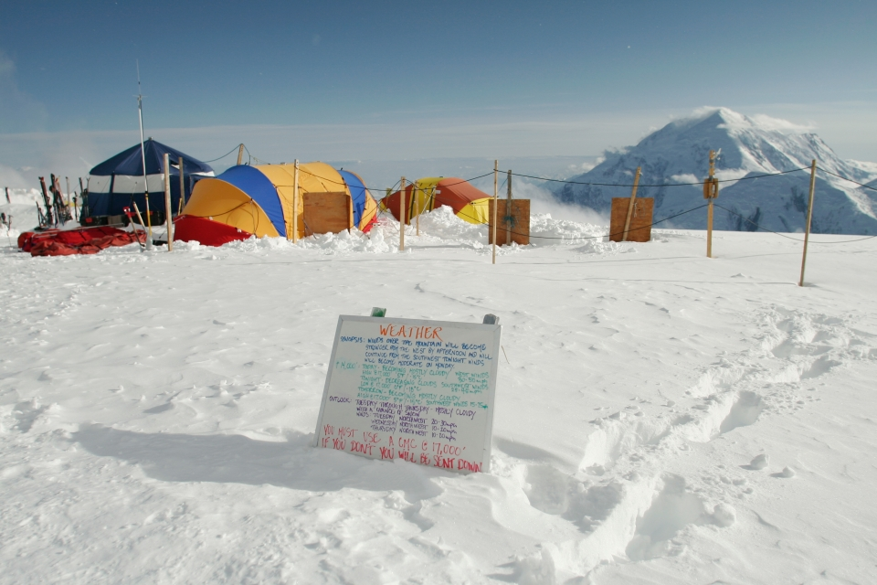 Whiteboard with weather information written in multiple colors sitting in the snow at a camp at Denali National Park & Preserve